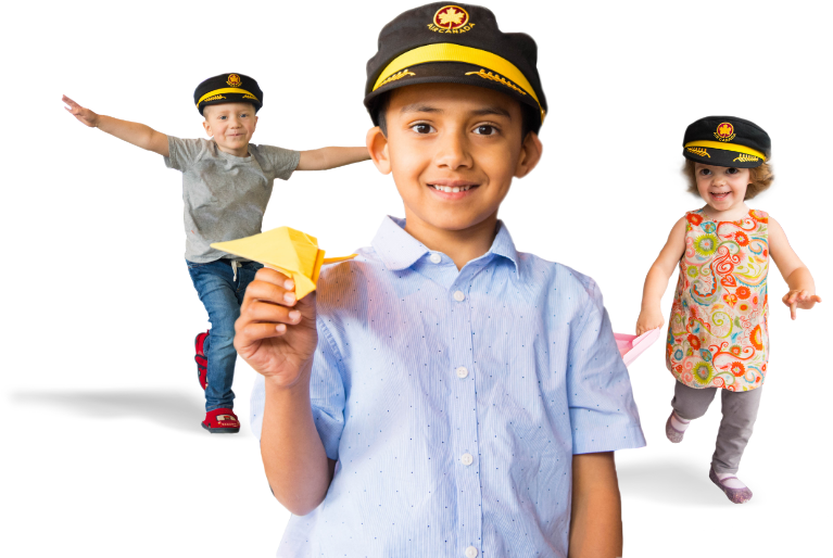 children holding paper airplanes and wearing captain's hats