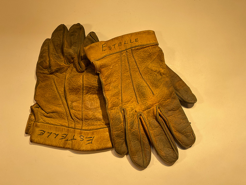 worn leather gloves with name Estelle written on cuffs