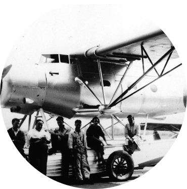 circle cropped black and white image of aircraft and people posing for photo