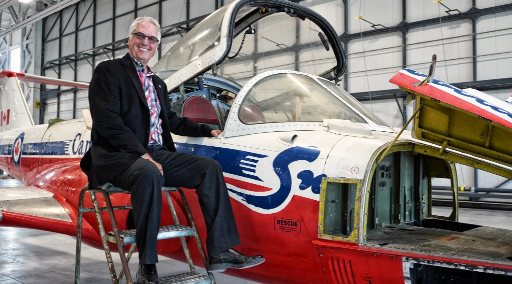 Bob sitting next to an airplane in the museum